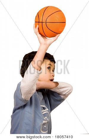 A young boy of mix parentage about to shoot basketball into the hoop, isolated on white.