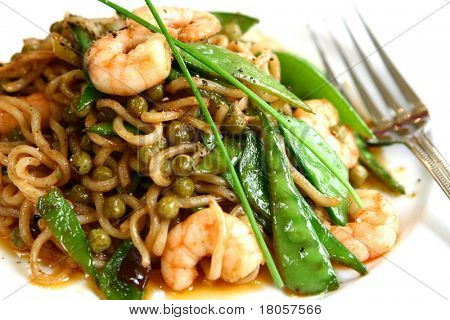 Close up of stir fried noodles with luscious prawns, peas, sugarsnap peas, garnish with chives. Absolutely delicious !