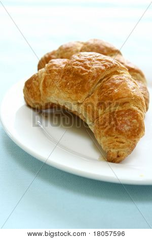 Two pieces of freshly toasted butter croissant served on white plate.