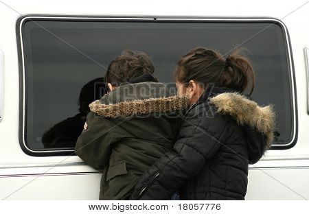 A little girl helping her curious brother up in peeping into the window of a limousine