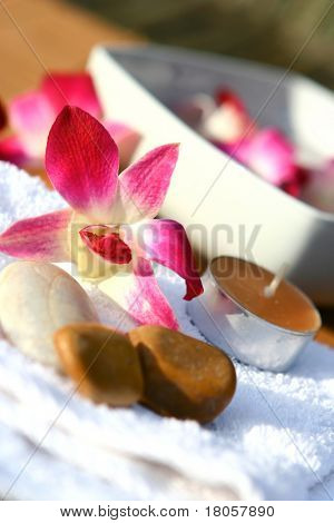 Orchid and candles for spa setting with white towel, displayed for an outdoor, evening massage session.