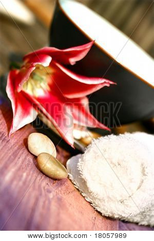 Bowl of floral water setting for spa with white towel, pebbles and single red tulip on rustic wood.