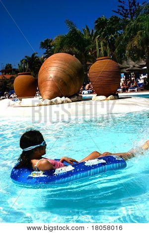 Junges Mädchen schwimmt auf Gummi-Ring, im tropischen Schwimmbad entspannen.