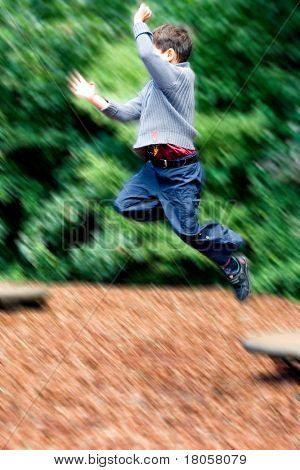 Young boy leaping high in the air, about to land on soft wooden chipping in the playground.