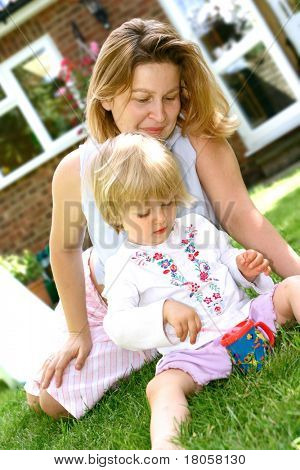 Mother watching her little girl toddler playing with soapy bubbles, outdoor in the garden.