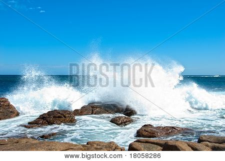 Waves crashing onto coastal rocks