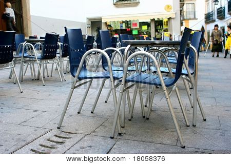Outdoor dining area made up of contemporary style metal seats on stoned paving.