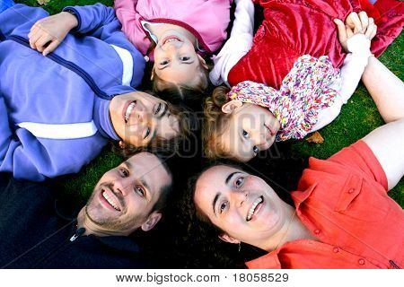 Young family with beautiful children in a head to head circle, lying on the grass.