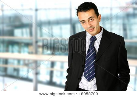 Confident young businessman in corporate interior with copyspace