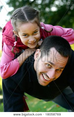 Young father lifting his daughter up on his back as they play together in the park