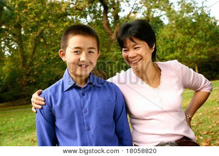 Thai mom sharing a joke with her young son from inter marriage, outdoor in an autumn park