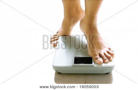 Pair of feminine feet about to stand on a weighing scale.