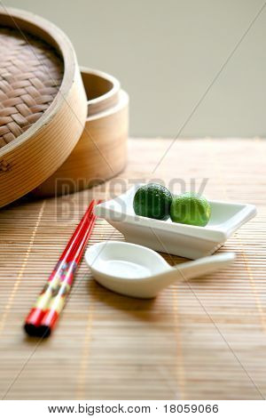 Two local calamansi limes in traditional Chinese setting with chopsticks and white china spoon on bamboo matting.