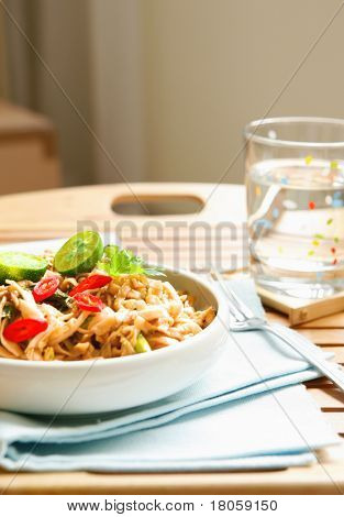 Delicious plate of stir fry noodles with vegetables and local limes with red chili.