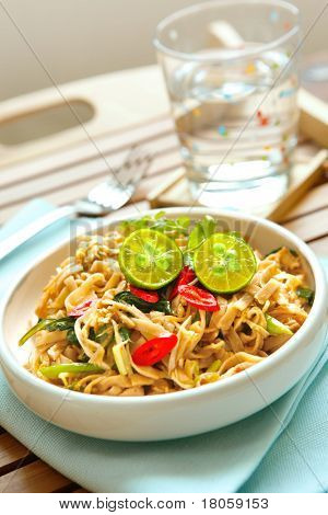 Plate of delicious stir fry chinese noodles with limes and chilis.