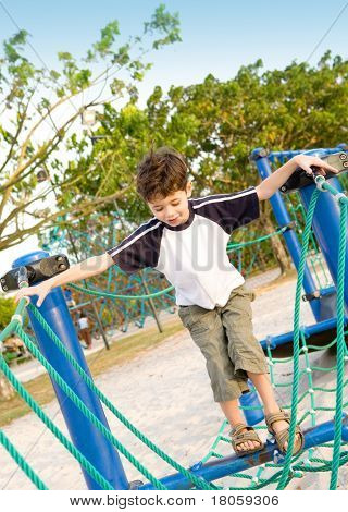 Young boy eager to cross the playground rope activity challenge.