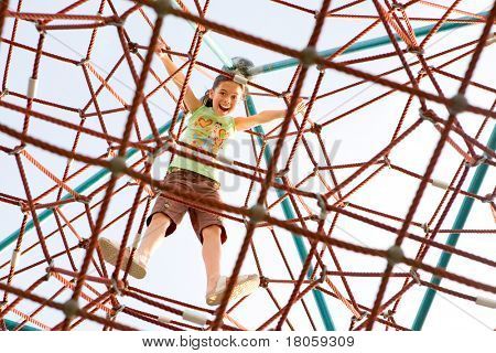 Young girl excited that she has reached the top of the giant climbing web activity.