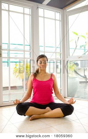 Young woman in sitting yoga stance in a calm and peaceful setting.