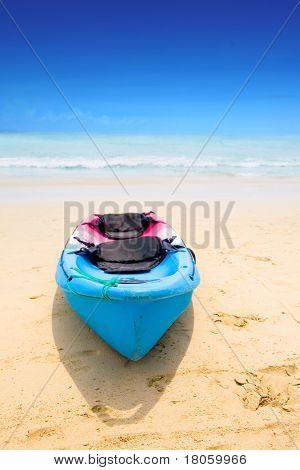 Blaue und rote Kanu von einem Sandstrand mit schönen blauen Himmel, die Auskleidung des weiten klaren Ozeans.