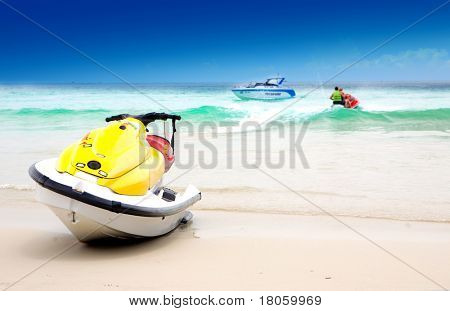 Jetski on sandy beach with crystal water and blue sky in background