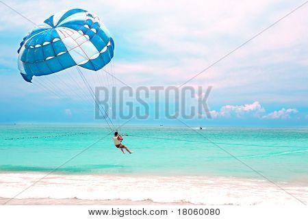 A man about to go up high paragliding from a tropical beach.