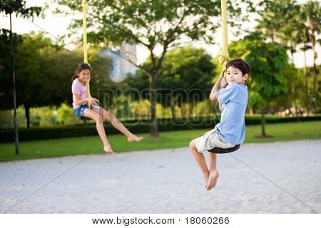 Two young children dangling on the suspension rope in playground