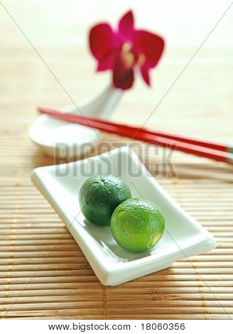 Two local calamansi limes in dipping bowl on table mat with chopstick and ceramic spoon on side.