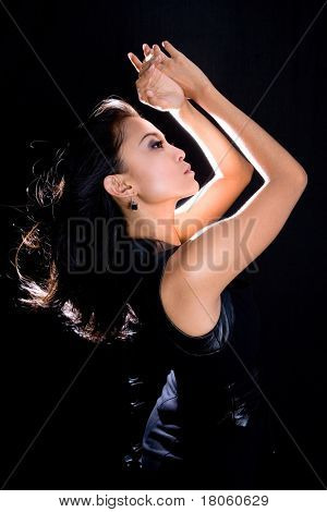 Young woman in black dress in lowkey lighting