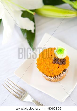 Pretty cupcake with orange icing and green flower biscuit.