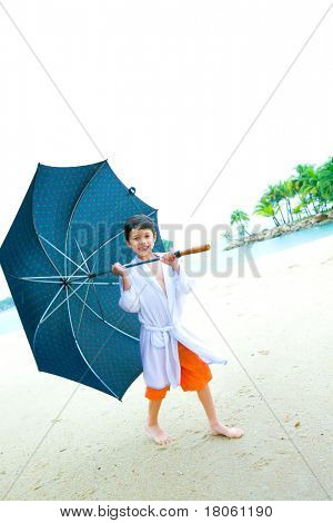 Cute little boy with a big umbrella having fun on the beach, in the rain
