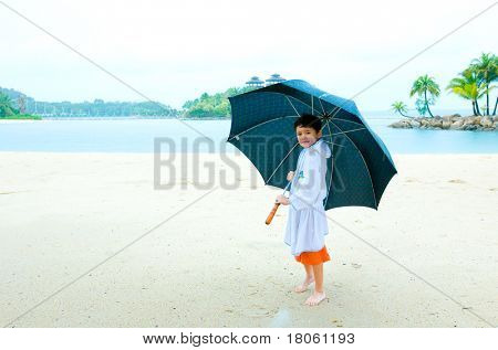 Young boy with big umbrella standing at the beach, in the rain