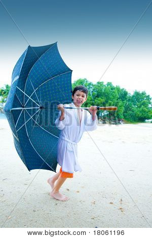 Cute little boy walking up the beach with a big umbrella in the rain