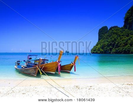 Long tailboats by the shore at Hong Island, Krabi Thailand against beautiful clear blue sky