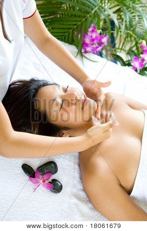 Woman enjoying facial therapy session in spa