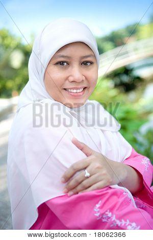 Bela mulher muçulmana malaia, sorrindo em um parque ao ar livre