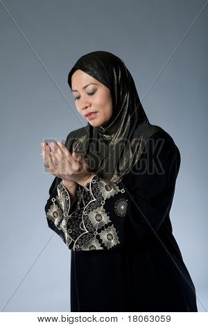 Muslim woman in traditional Islamic clothing made out of full suit covering the body and headscarf praying and wishing