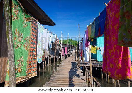 Colorful washing lining a wooden boardwalk of a water's village near Tuaran, Sabah Malaysia.