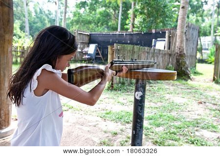 Young girl aiming target with rifle at sports centre.
