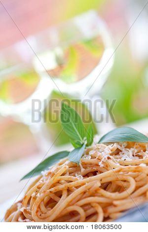 A plate of spaghetti with tomato sauce in an outdoor setting.