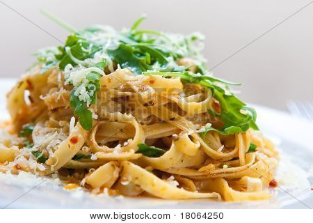 Delicious fettucine pasta with sundried tomato and rocket leaves