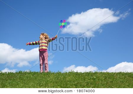 Girl stands on grass in summer looks aside and holds windmill  in  hand