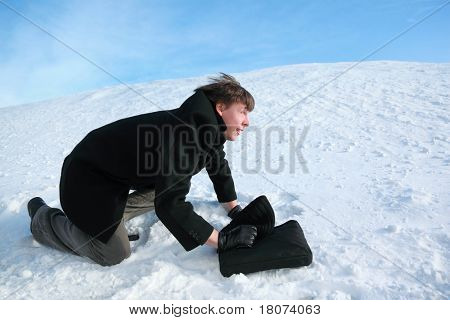 Young man creeps on all fours on snow with  brief-case