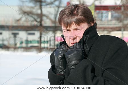 Young man froze in winter and hides head in collar