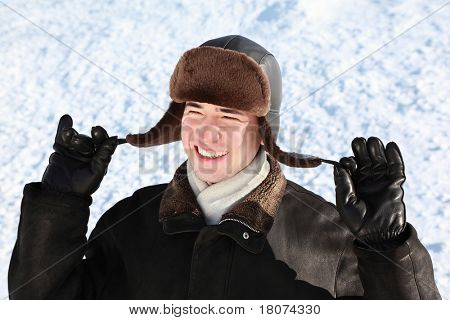 Boy holds on cordages ear-flaps hat