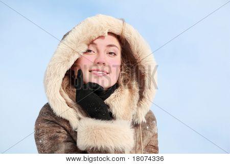 Retrato da menina que inclina-se o queixo na mão no inverno