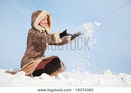 Mãos e jovem mulher de cócoras atiram neve