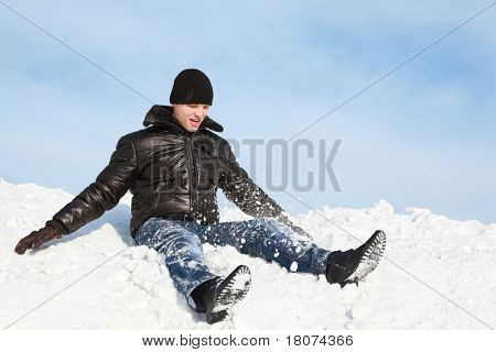 Youth sits in winter on snow and throws him up