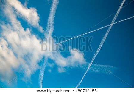 contrails of jet planes and clouds in blue sky