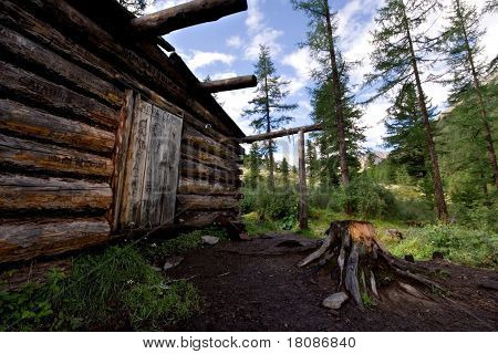 Wood shack (izba, winter hut, log house) in wild forest, Sayan Mountains, Buryat Republic, Russia. N
