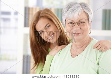 Portrait of elderly mother and daughter smiling happily.?
